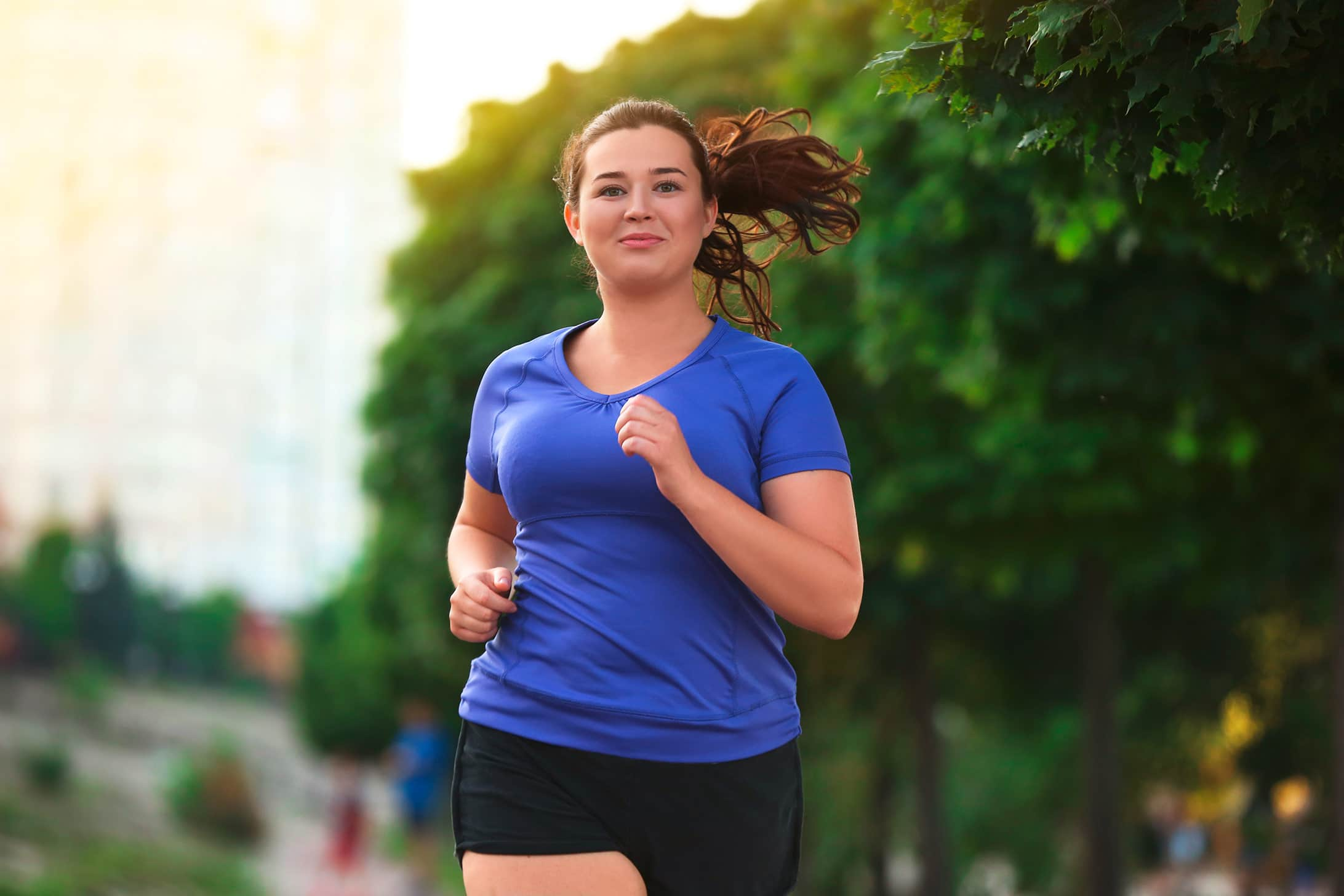 Bild einer Frau welche durch die Stadt joggt.