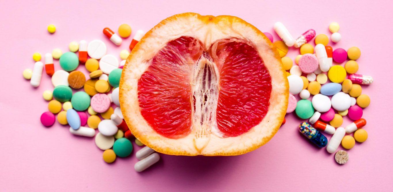 Eine aufgeschnittene Grapefruit mit vielen verschiedenen Tabletten rundherum.