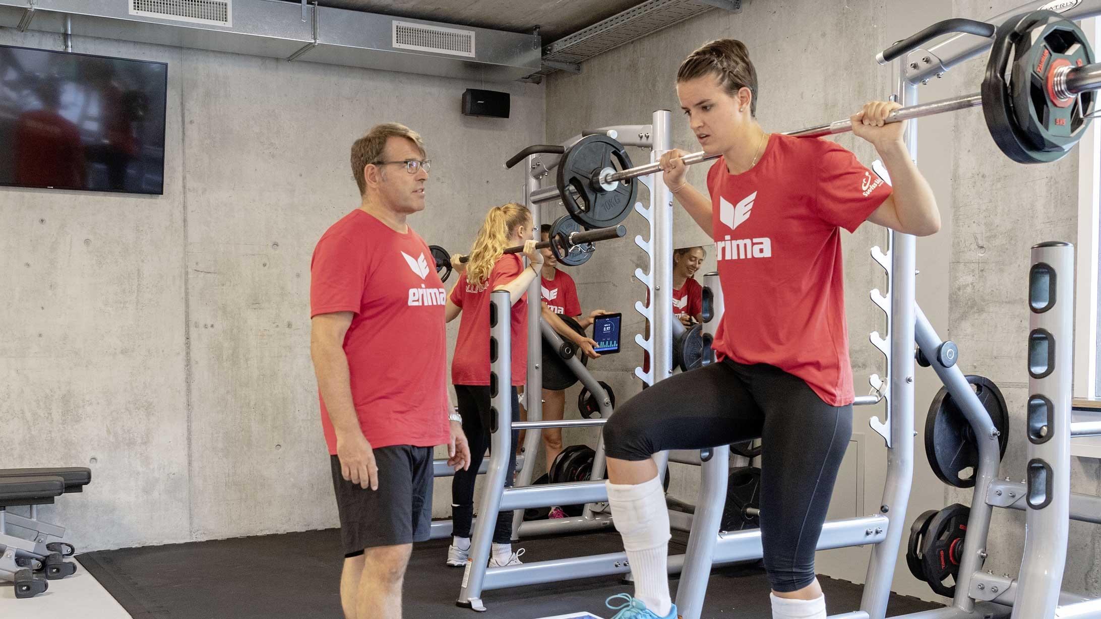 Sporttherapeut Jürgen Schreier überwacht das Hanteltraining einer Frau der Schweizer Volleyball-Nationalmannschaft.