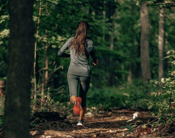 Eine Frau joggt auf einem Waldweg.