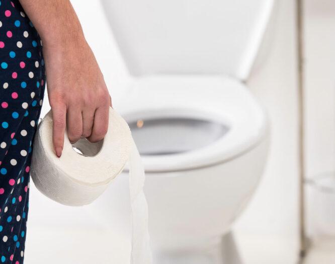 Jemand steht mit einer Rolle Toilettenpapier vor der Toilette.