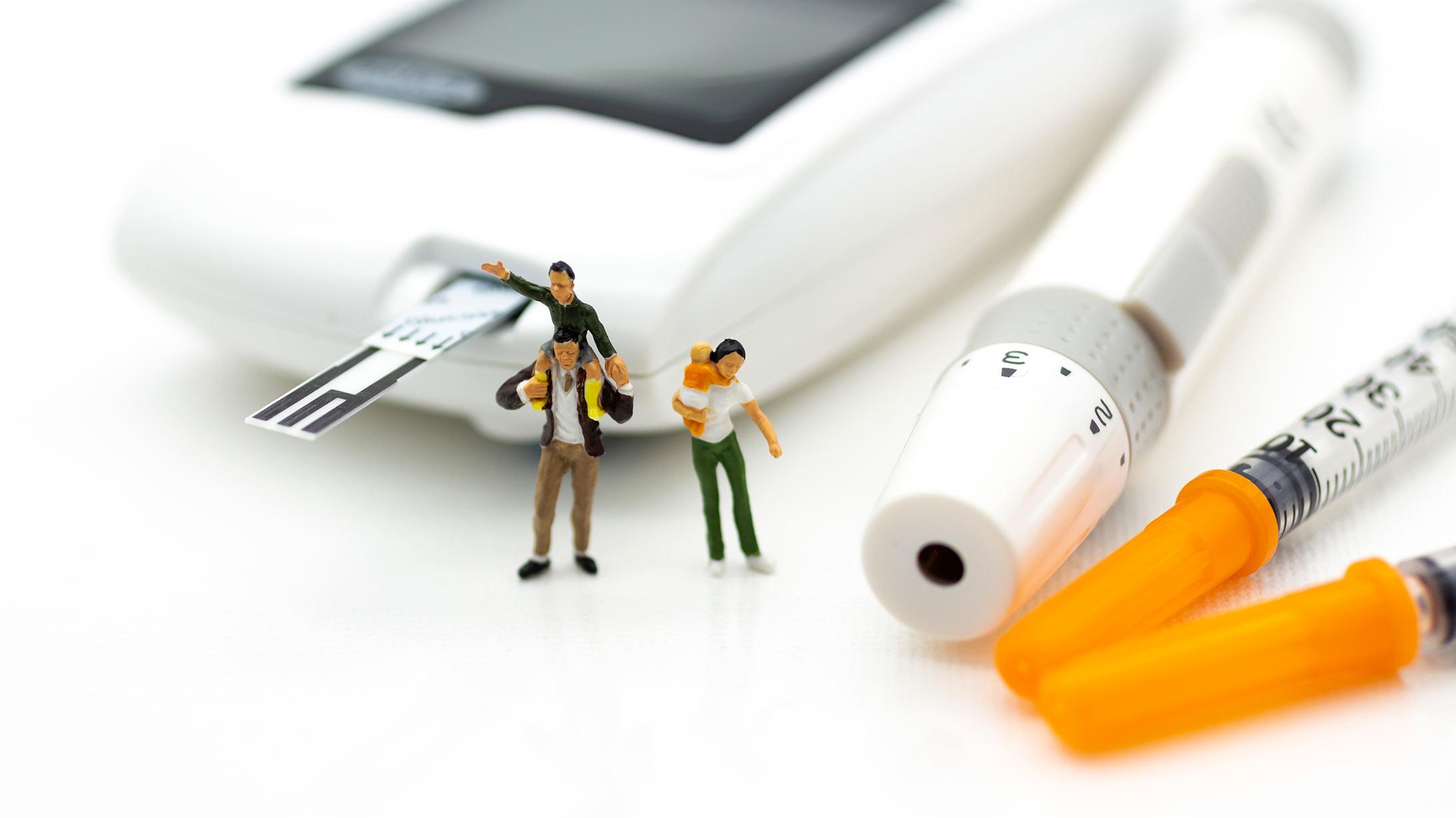 Diabetes Typ 1: Spielfiguren neben einer Insulinspritze