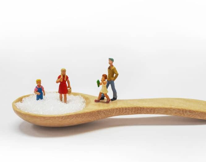 Diabetes Typ 1: Spielfiguren stehen auf einem mit Zucker gefüllten Holzlöffel