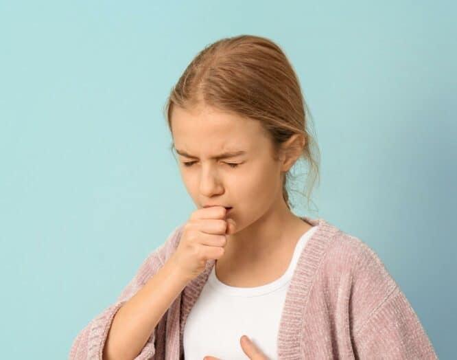 Ein Mädchen hält sich beim Husten die Hand vor den Mund