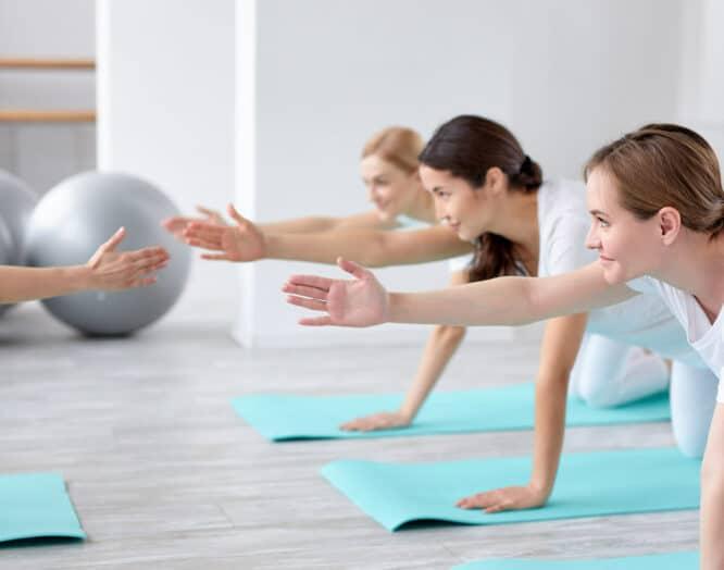Eine Gruppe junger Frauen macht in einem Fitnessraum Übungen auf Yogamatten