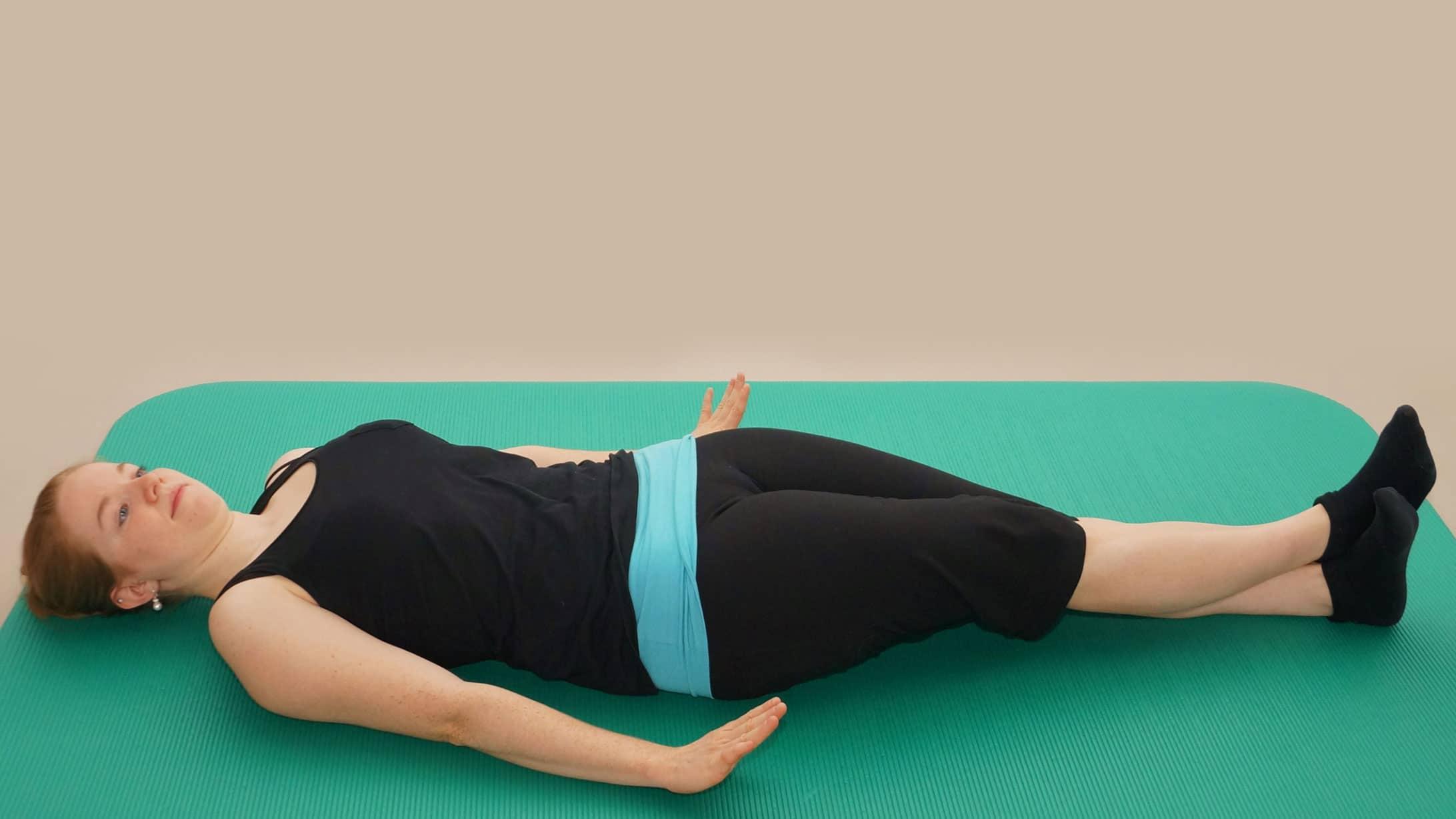 Rückbildungsgymnastik: Eine junge Frau liegt mit ausgestreckten Armen und überkreuzten Beinen auf einer Yogamatte.
