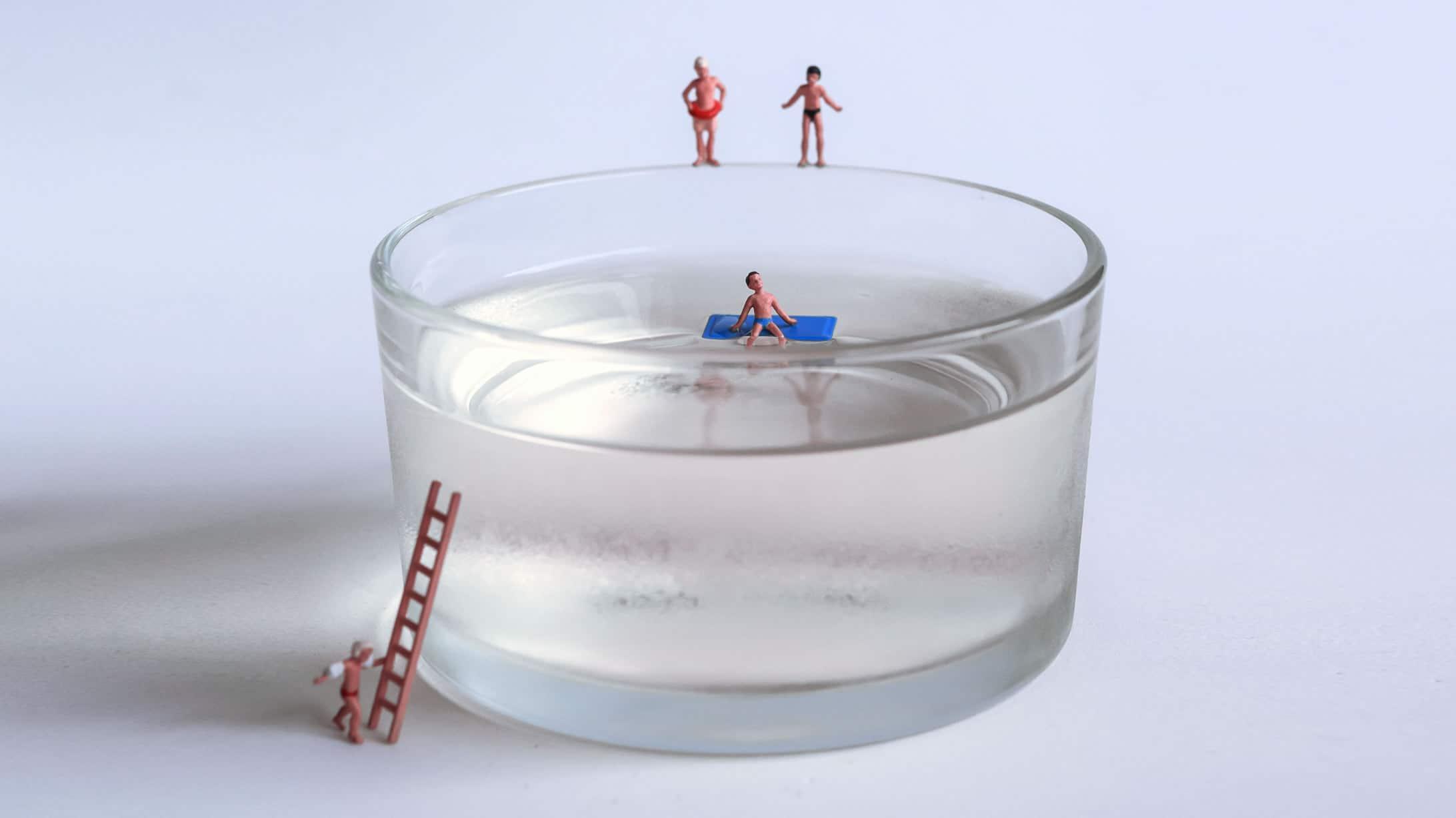 Ein Wasserglas mit mehreren kleinen Plastikfiguren auf dem Glas und im Wasser