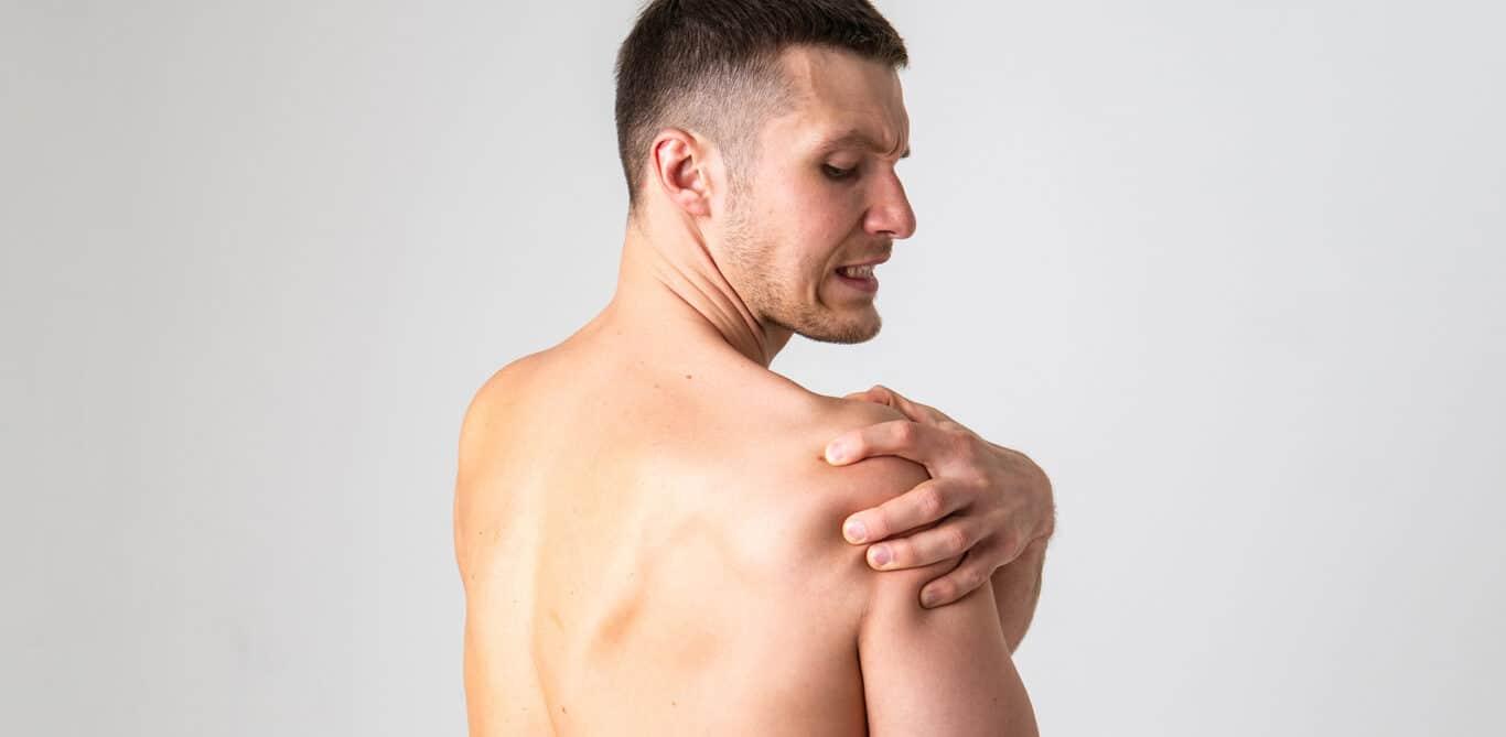 Ein Mann fasst sich mit schmerzverzerrtem Gesicht an die Schulter.