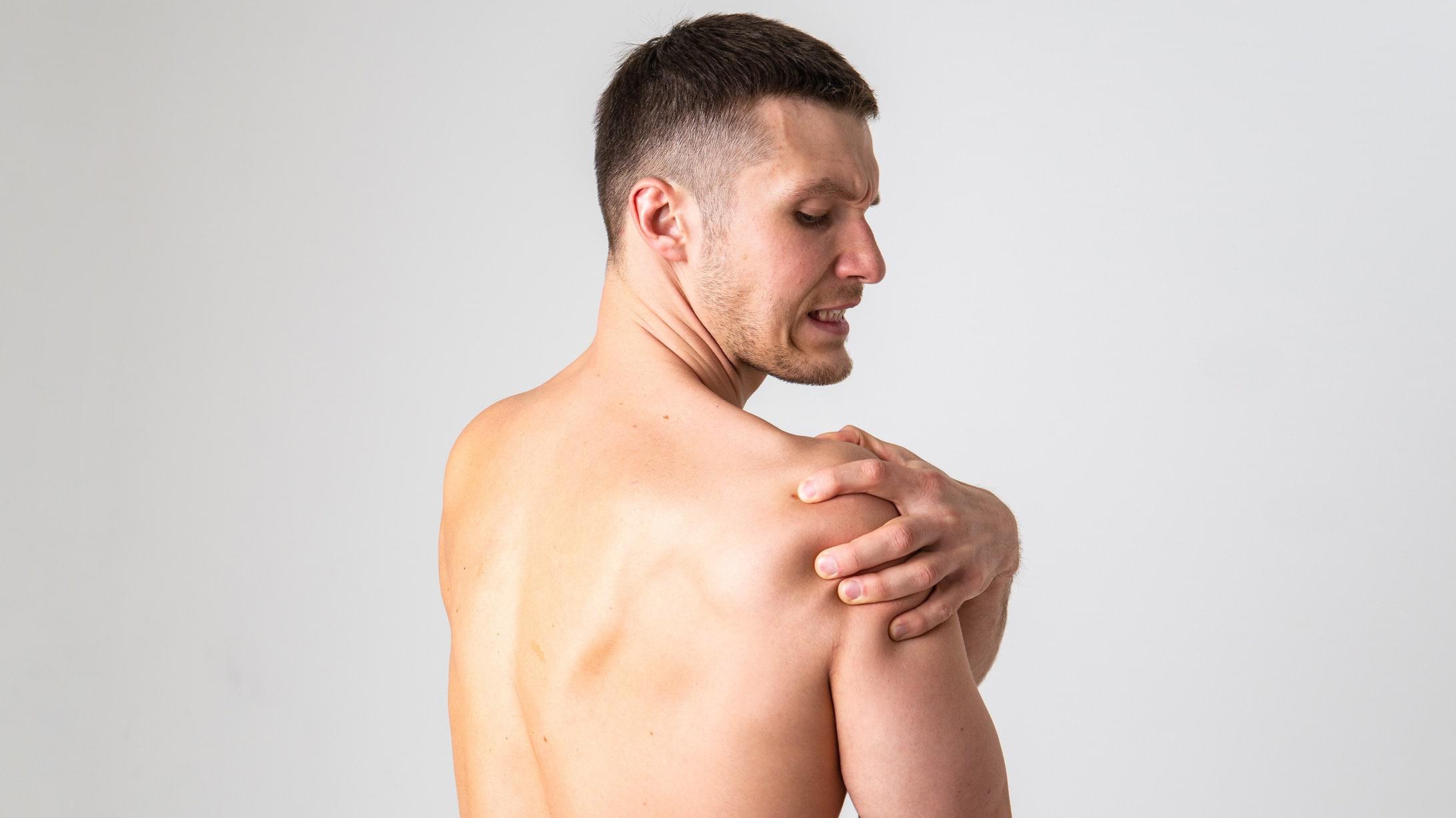 Ein Mann fasst sich mit schmerzverzerrtem Gesicht an die Schulter. Symbolbild für Impingement an der Schulter.