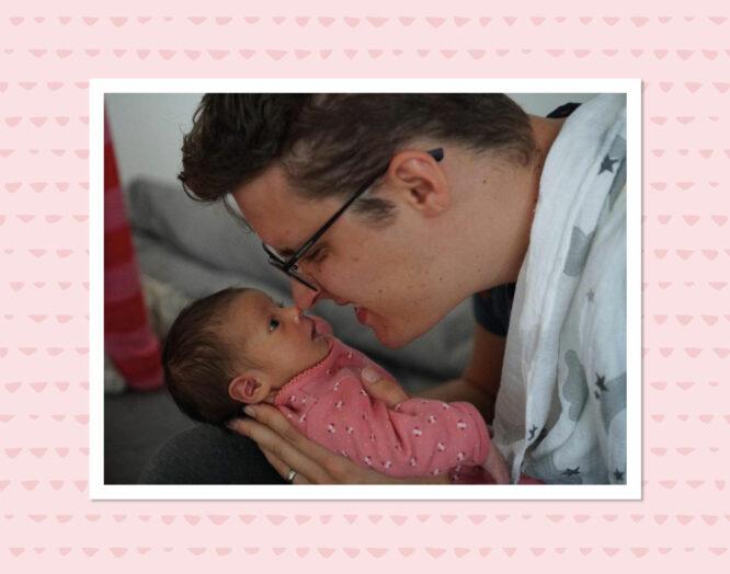 Ein junger Vater hält seine neugeborene Tochter ans Gesicht.