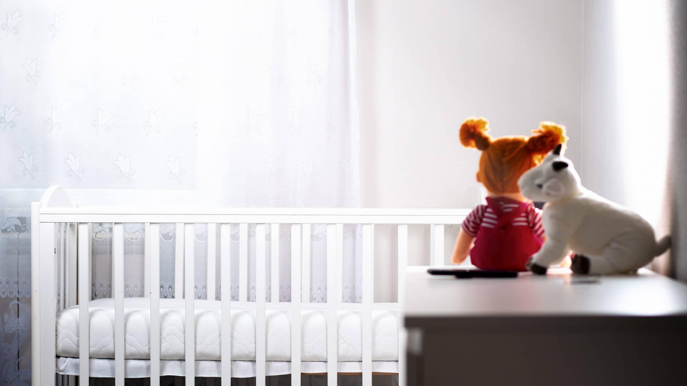 Fehlgeburt: Ein leeres Kinderzimmer mit einem Bett mit Laufgitter und zwei Stofftieren.