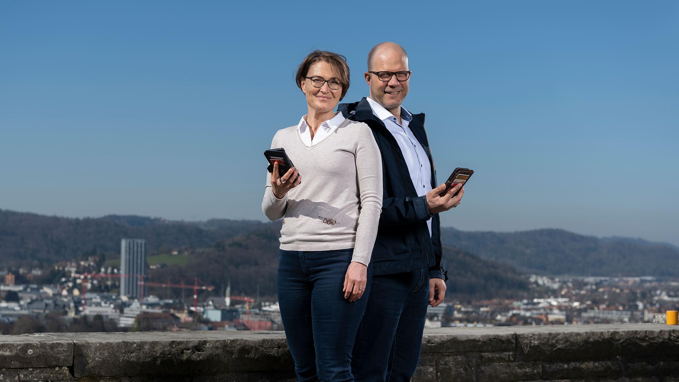 Das Foto zeigt die beiden Entwickler der App für Patientendaten, Infos, und Termine «heyPatient», Regula und Matthias Spühler. Beide halten ein Smartphone in der Hand.