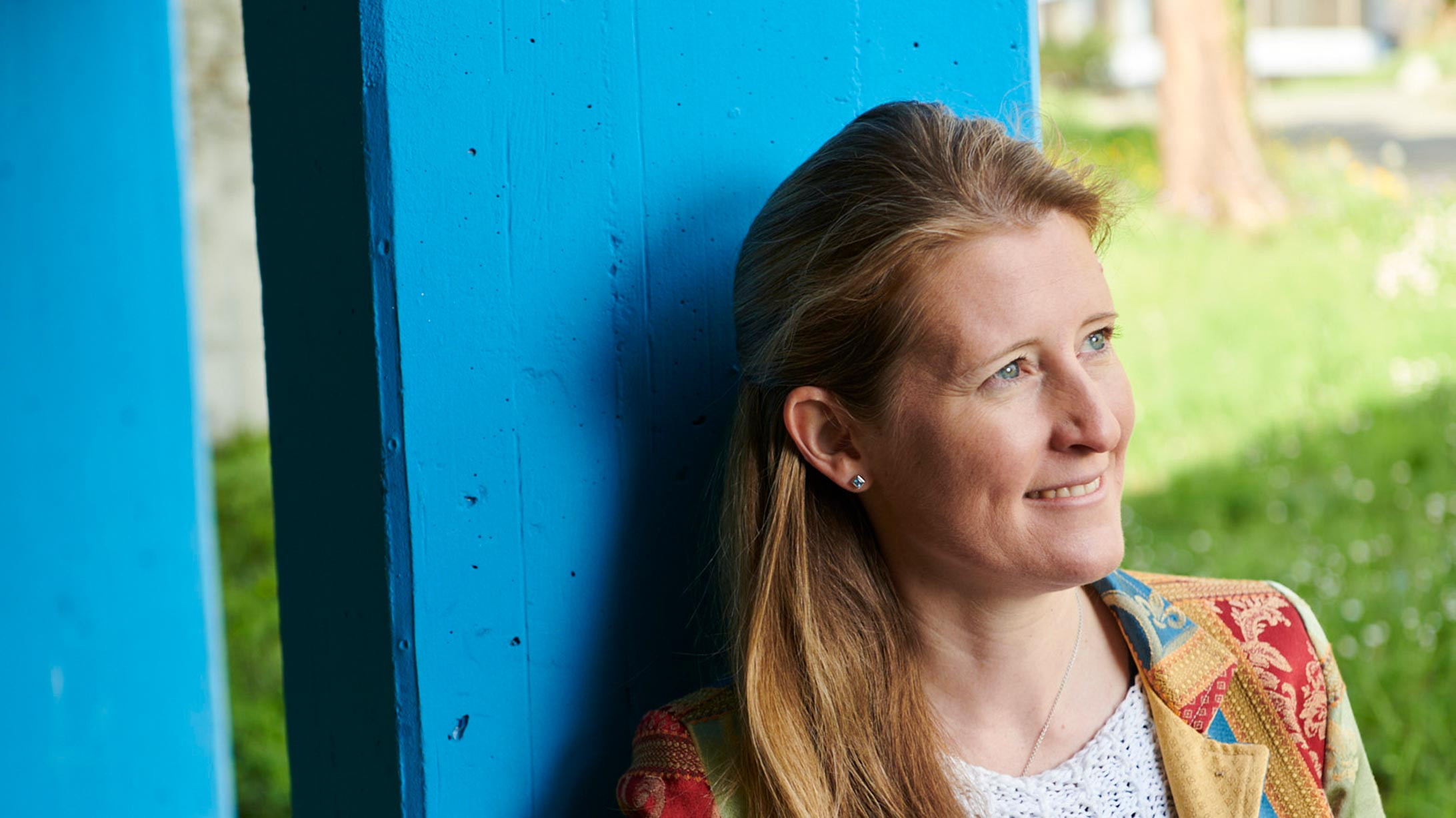 Irene Burger lehnt an eine blaue Säule