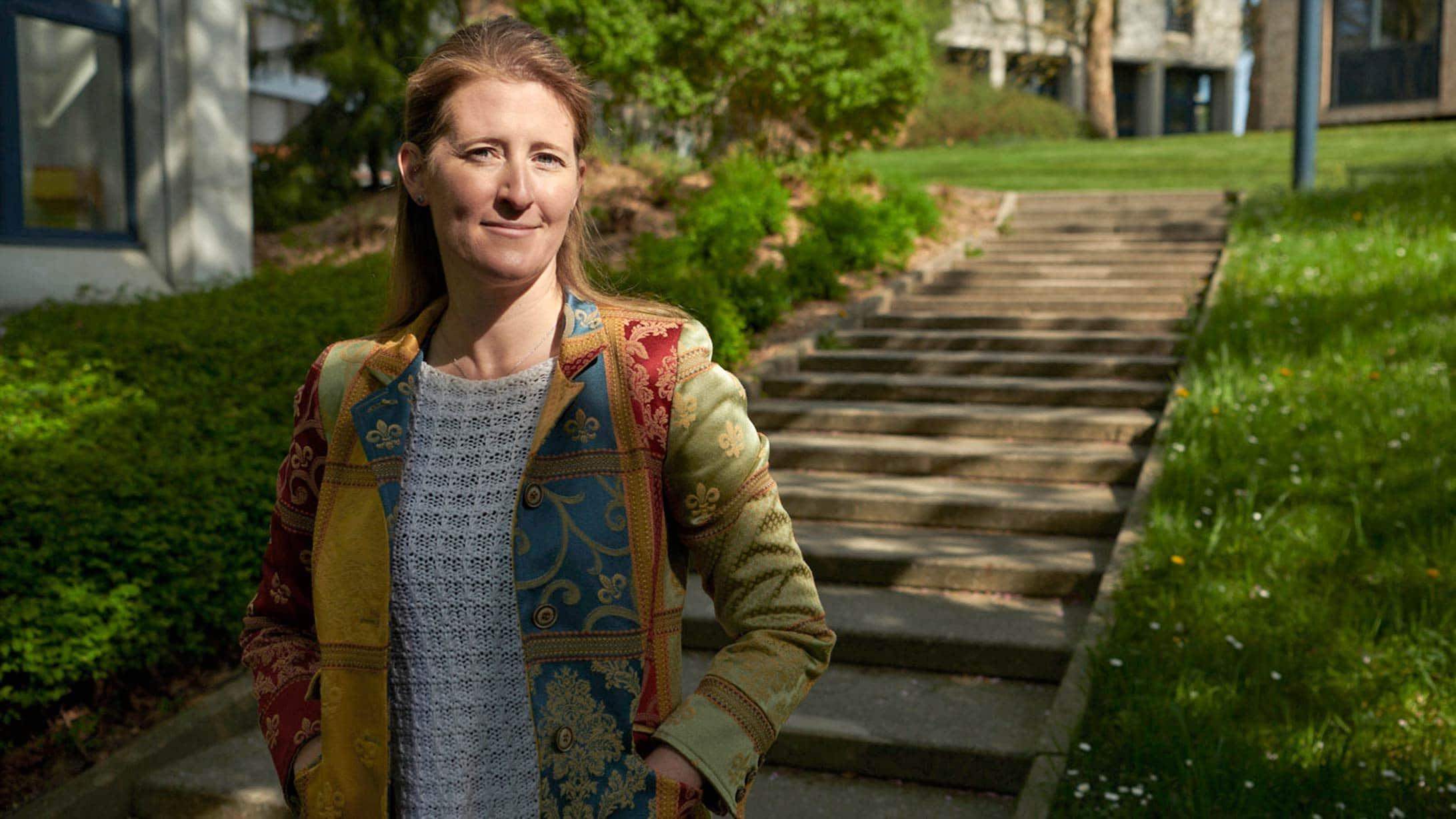 Irene Burger steht vor einer Treppe in einer Parkanlage