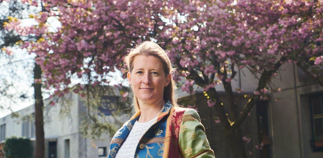 Portrait von Irene Burger vor einem blühenden Baum.