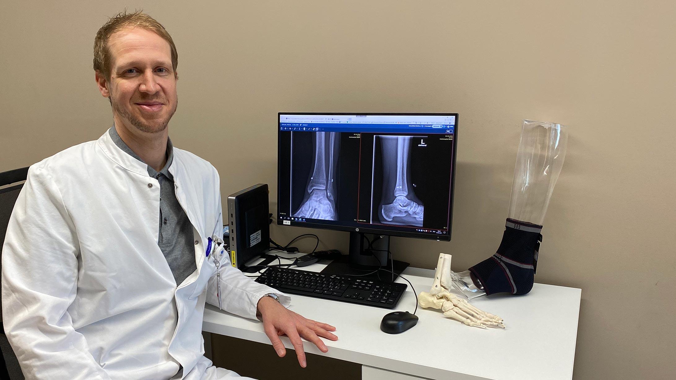 Fusschirurg Christopher Lenz sitz vor einem Bildschirm mit Röntgenaufnahmen eines Fusses.