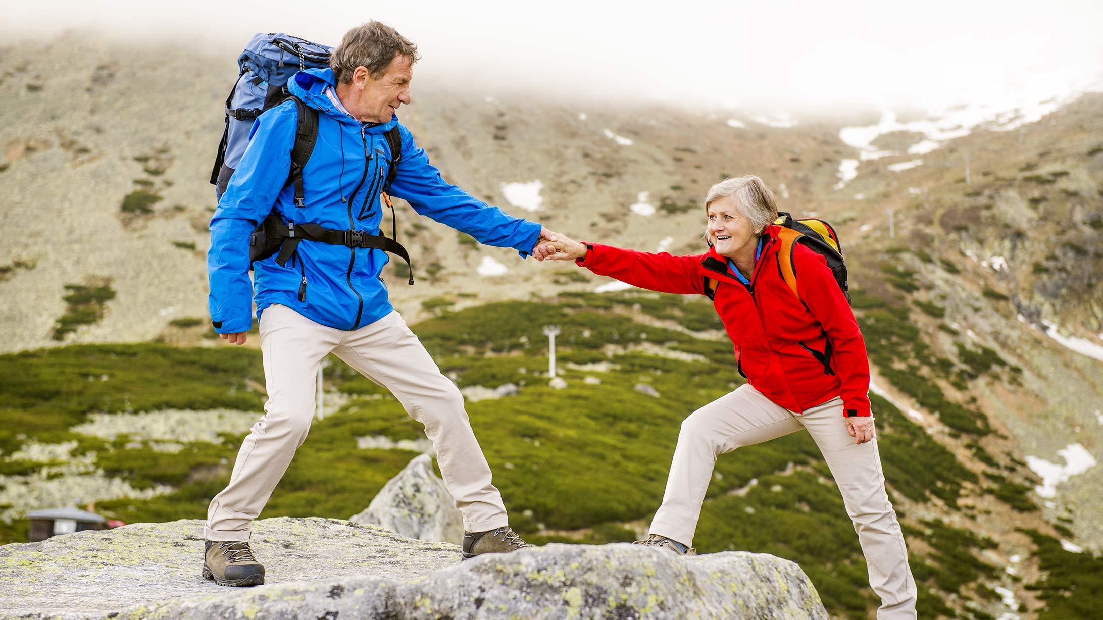 Ein älteres Paar klettert beim Wandern auf einen Felsen.