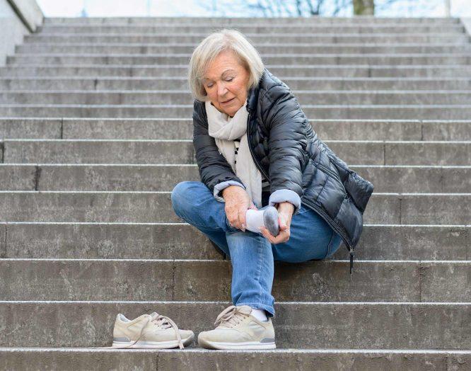 Eine Frau sitzt auf einer Treppe und hält sich Fuss und Knöchel