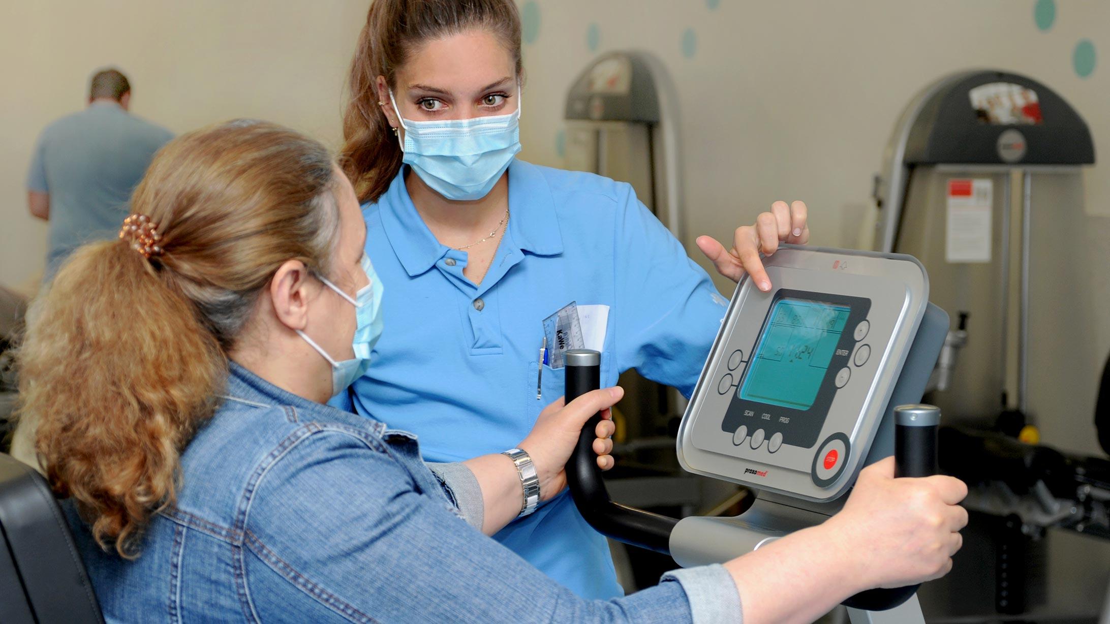 Chiara Scherrer, Praktikantin Physiotherapie, erklärt einer Patientin ein Gerät.